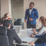 Inclusive Leadership article image of conference room with one man standing and several other business personnel sitting and listening
