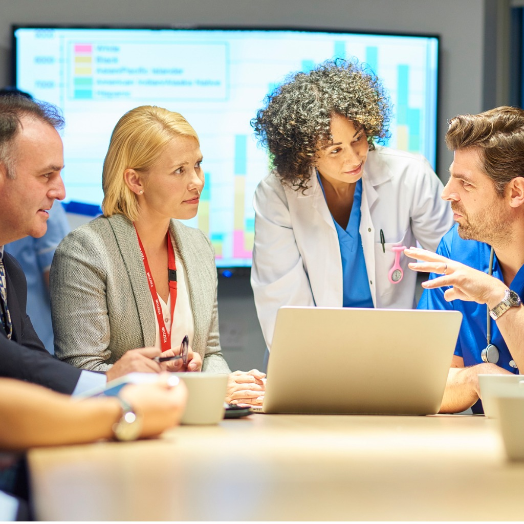 a mixed group of healthcare professional and business people meet around a conference table.