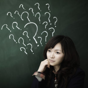 Young woman with question marks drawn on chalkboard behind her