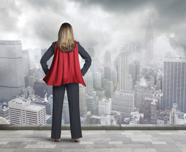 A rear view of a businesswoman wearing a red cape looking out over the city below her. She is standing her hands on her hips as a gentle breeze flows through the cape. A gray sky and patchy clouds hover over the city in the distance.