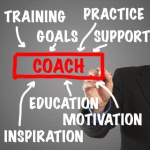 Male hand in business wear holding a thick pen, writing on an imaginary screen at the camera: Elements of being a coach