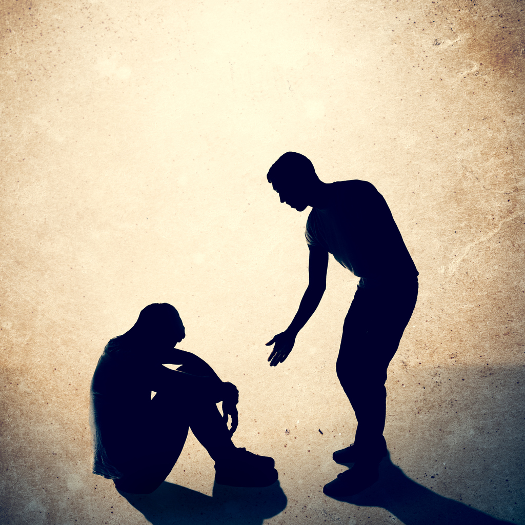 A silhouette of a man reaching out to help assist another person who is sitting on the ground