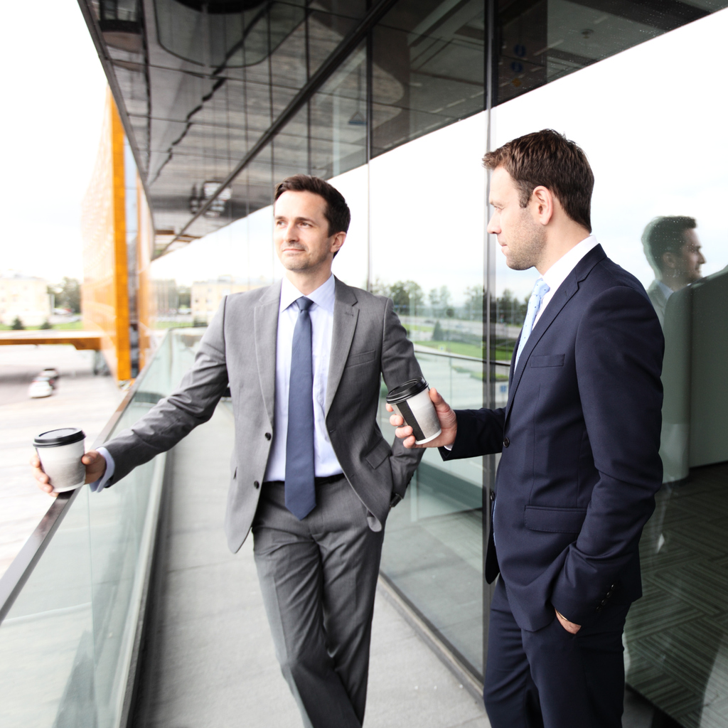 Two business people with coffee chatting on balcony of office building