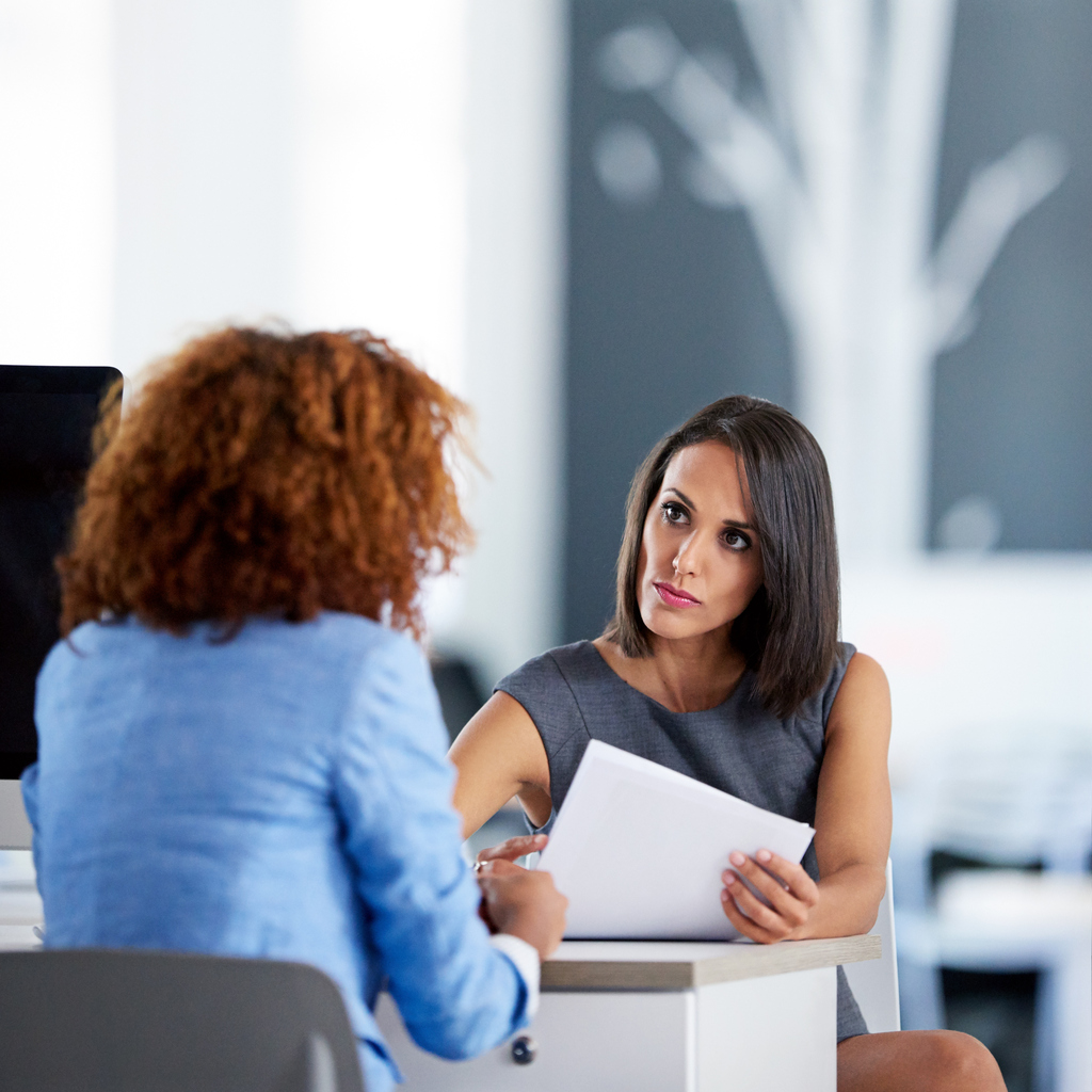 Shot of two young businesswomen talking together at a desk in an office