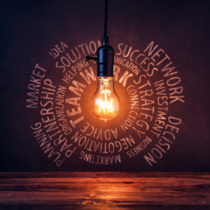 Still life photography of a hanging, lit vintage light bulb. Business phrases chalk drawing. Smudged blackboard background and wooden desk.
