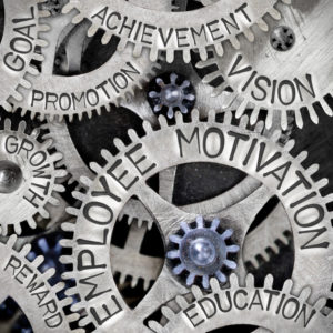 Macro photo of tooth wheel mechanism with EMPLOYEE MOTIVATION, VISION, EDUCATION, GOAL, REWARD, GROWTH, ACHIEVEMENT and PROMOTION words imprinted on metal surface