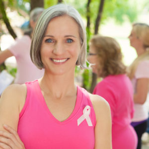 Happy mature Caucasian woman participates in a breast cancer awareness fun run. She is wearing a pink tank top with breast cancer awareness ribbon.
