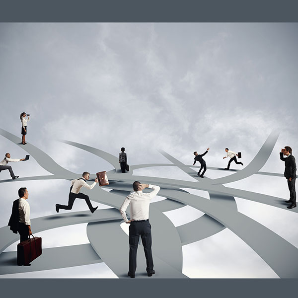 multiple businesspeople in front of cloudy background on a series of winding, confusing paths