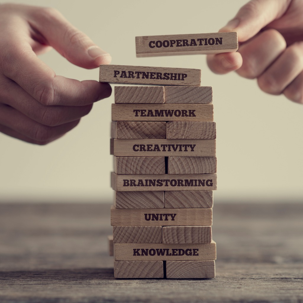Close-up of hands putting dominoes onto stack of wooden bricks with motivational business phrases, like teamwork, creativity, on brown table surface, vintage effect toned image.