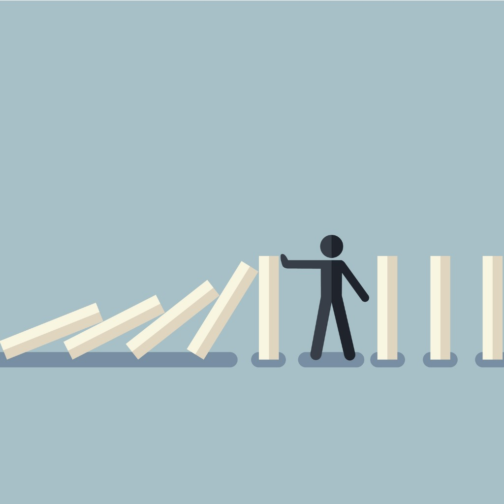 A stick figure stopping the domino effect with falling white dominoes