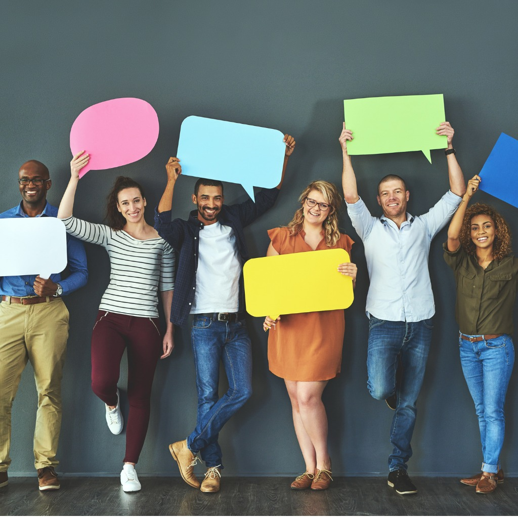 A diverse group of people holding up speech bubbles against a gray background
